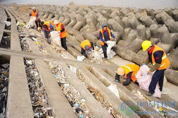 太仓环卫工人在清理冲到江边的垃圾