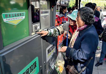 ▲4月10日,北京市东城区某小区居民在体验智能垃圾分类箱 李欣摄/本刊