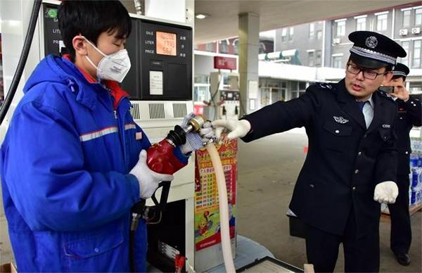 北京市生态环境局执法人员在一加油站检查油气回收装置运行情况。